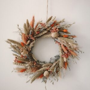 a dried flower wreath in oranges, turquoises and blues